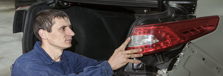 car mechanic removing rear light on a car