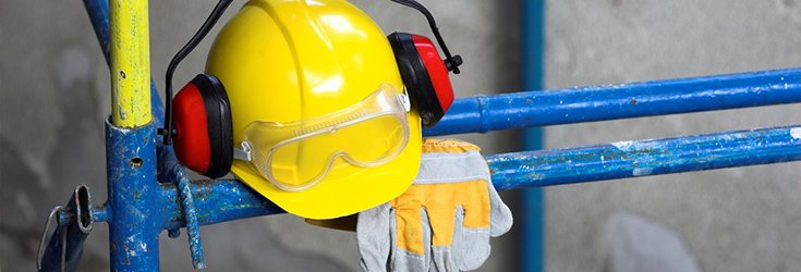 hardhat and safety gloves on scaffold tower