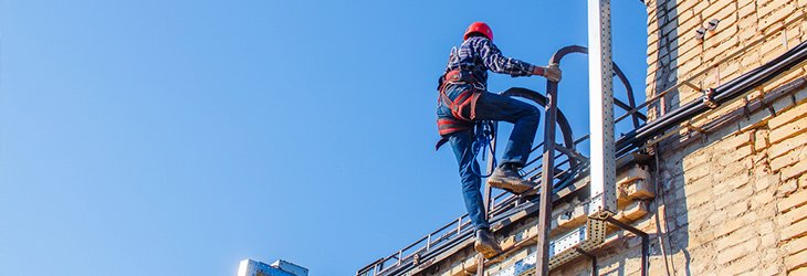 man climbing external building with safety PPE