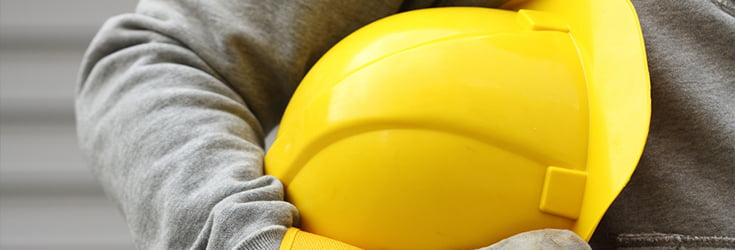 person holding yellow hard hat